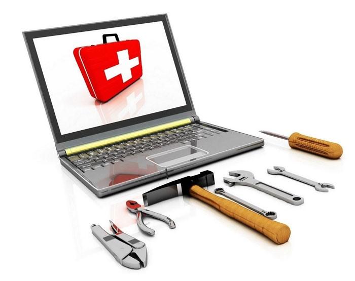 на экране ноутбука изображение аптечки и рядом с ноутбуком лежат инструменты